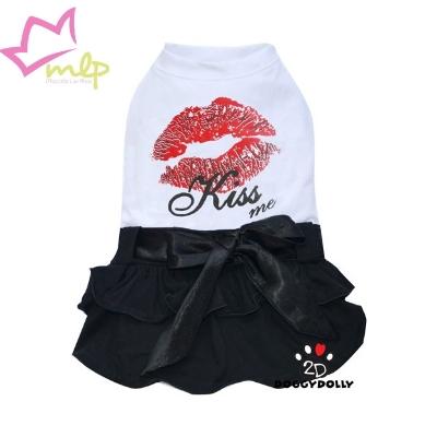 """Vestido Kiss Me de color blanco y falda de color negro con un chulísimo lazo. Estampado de un beso con la orden """"Kiss me"""" (Bésame). Una prenda original y moderna para nuestras pequeñas peludas."""