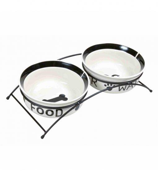 Comedero y bebedero cerámica. Dos comederos para perros, elaborados en cerámica, con soporte metálico lacado en color negro. Antideslizante de caucho en la base. Ideal para proporcionarle el alimento a tus perros de manera efectiva y adecuada. La cerámica mantiene la temperatura de la comida y el agua. Los comederos van de corados con dibujos en negro con el fondo blanco. Disponible en dos tamaños. Pequeño -- 0,25L - 13cm de diametro Mediano -- 0,6L - 15cm de diametro
